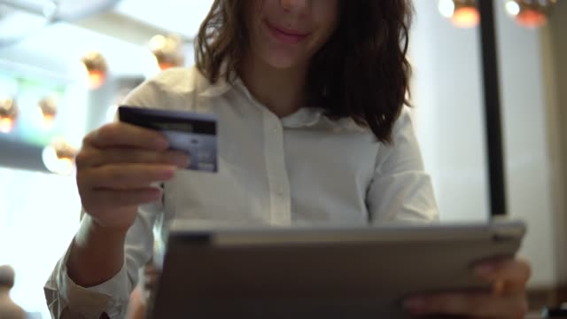 young asian girl shopping on mobile phone with credit card in cafe - ordering stock videos & royalty-free footage