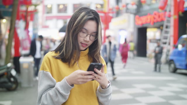 young asian girl using mobile phone in ximending - traditionally vietnamese stock videos & royalty-free footage