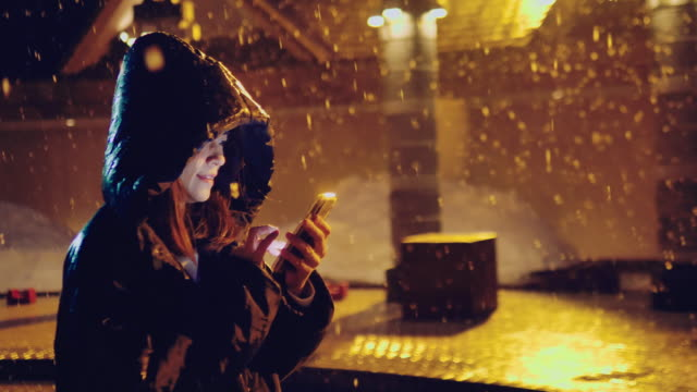 junges asiatisches mädchen mit handy auf der winterstraße mit weihnachtsbeleuchtung - sturm frau stock-videos und b-roll-filmmaterial
