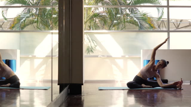 Young asian good looking woman practicing yoga alone in yoga studio
