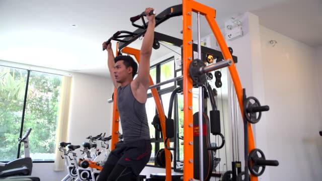 stockvideo's en b-roll-footage met jonge aziatische knappe man doen oefeningen in de sportschool - fitnessapparatuur