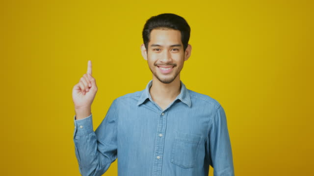 young asian handsome man is smiling and counting on his fingers up to 3, happy asia man looking at camera and showing one, two, three hand sign while standing over yellow background in studio, head shot - plain background stock videos & royalty-free footage