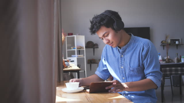 young asian handsome man listening to music with headphone and drinking a cap of coffee while reading a book at home, people relaxing lifestyle and technology concept - asian stock videos & royalty-free footage