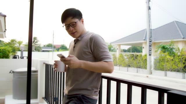 vídeos y material grabado en eventos de stock de joven asiático guapo sonriente hombre utiliza smartphone mientras se relaja en el balcón en su casa. uso de redes sociales en el hogar. - un solo hombre de mediana edad