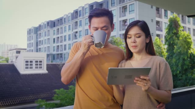 young asian happy couple relaxing with coffee and using digital tablet on roof terrace with city in the background - balcony stock videos & royalty-free footage
