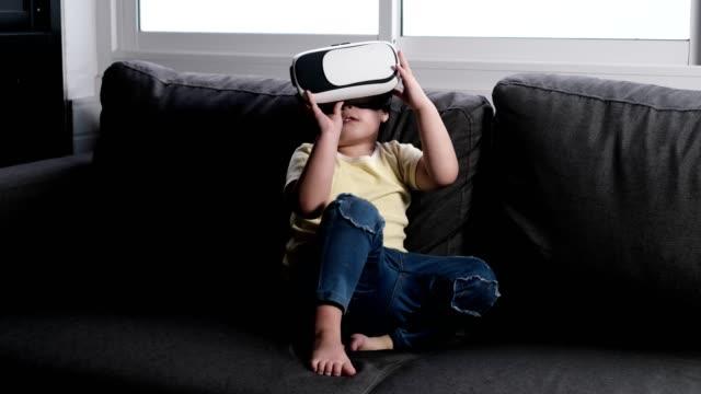 vidéos et rushes de jeune fille asiatique d'enfant utilisant le casque de réalité virtuelle - seulement des petites filles