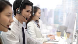 Young Asian male telemarketer with colleagues in call center city office