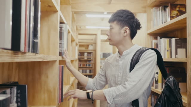 young asian male university student looks for a book in the library (slow motion) - taipei stock videos & royalty-free footage