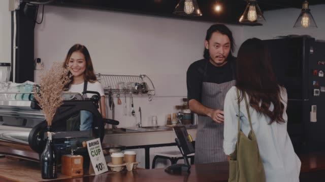 vídeos de stock, filmes e b-roll de o avental asiático novo do desgaste do barista do homem e da mulher que prende o copo de café quente serviu ao cliente no balcão da barra na cafetaria com face do sorriso. conceito do pequeno negócio do café e da cafetaria. - pequeno