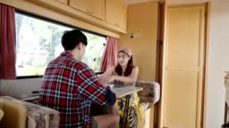 Young asian man baked food for his girlfriend while her working on laptop in camper van