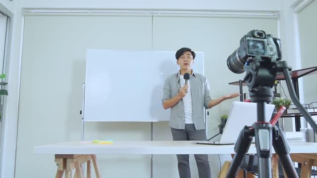 若いアジアの男性ブロガーがvlogビデオを記録し、インフルエンサーはスタジオでソーシャルメディア上でライブストリーミング、学習のためのチュートリアルオンライン - バイラルビデオ点の映像素材/bロール