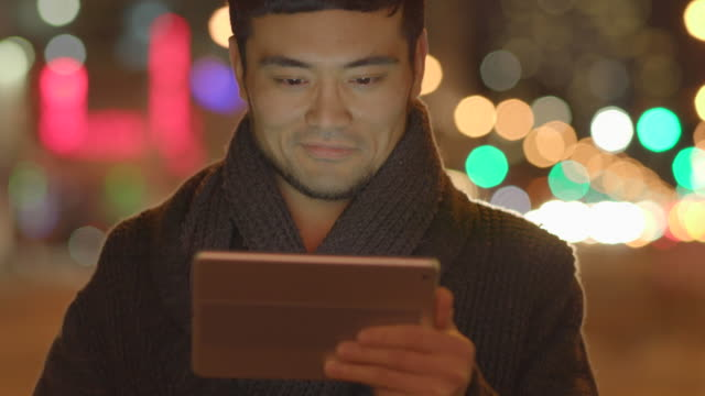 young asian man browsing the web online using smart phone tablet pc