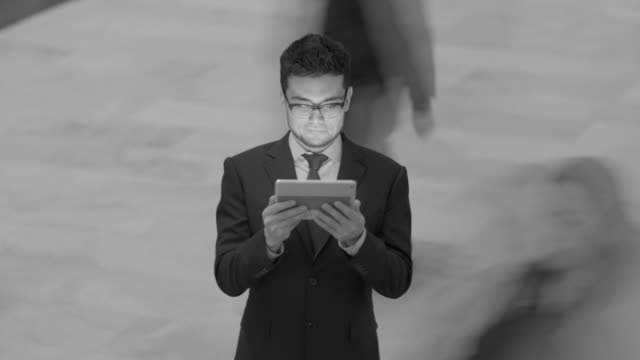 young asian man browsing the web online using smart phone tablet pc - standing out from the crowd stock videos & royalty-free footage