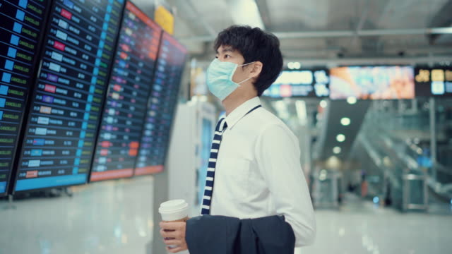 young asian man checking departure board with smart phone at the airport - full suit stock videos & royalty-free footage