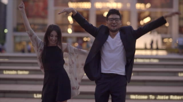 young asian man dancing with cauasian women in the city at night