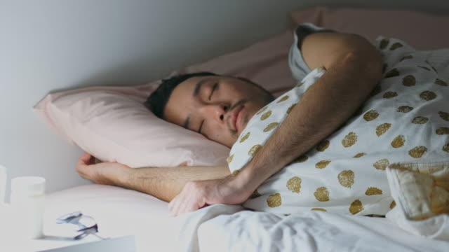 junge asiatische mann tief schlafen mit bequem im bett - tiefe stock-videos und b-roll-filmmaterial