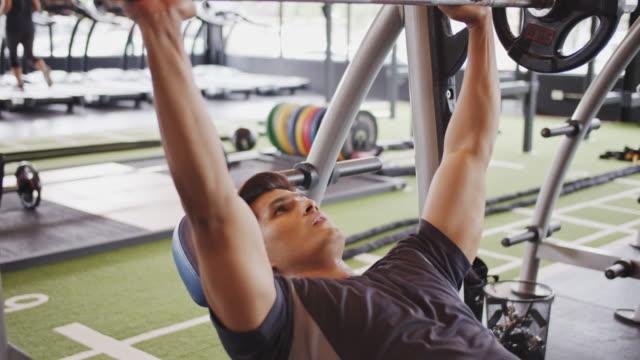 vídeos y material grabado en eventos de stock de 4k uhd : joven asiático haciendo ejercicio con pesas barbell en el gimnasio - press de banca