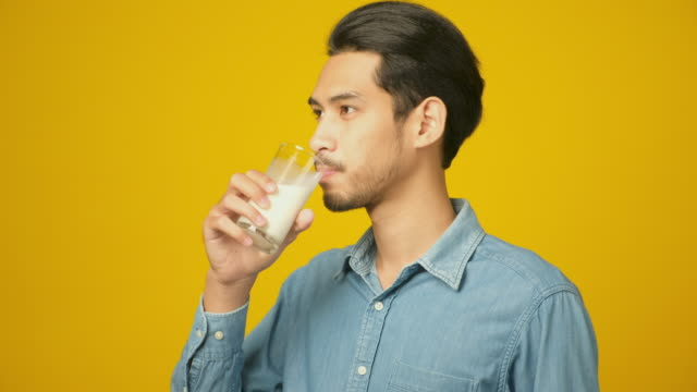 young asian man drinking milk while standing over isolated yellow background, food and drink , people and healthy lifestyles - soy milk stock videos & royalty-free footage