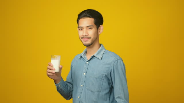young asian man drinking milk while standing over isolated yellow background, food and drink , people and healthy lifestyles - soy milk almond milk stock videos & royalty-free footage