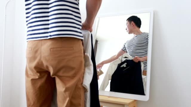 stockvideo's en b-roll-footage met jonge aziatische man passen van de jurk in zijn huis. -stock video - moving past