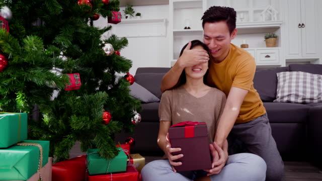 stockvideo's en b-roll-footage met jonge aziatische man geeft kerstcadeau verrassing voor zijn vriendin in de huiskamer, concept van kerst vakantie - kerstman