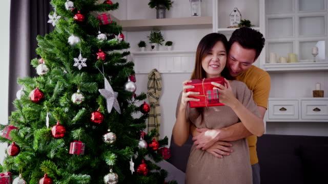junge asiatische mann gibt weihnachtsgeschenk überraschen, seine freundin im wohnzimmer zu hause weihnachten urlaub konzept - asiatisch stock-videos und b-roll-filmmaterial