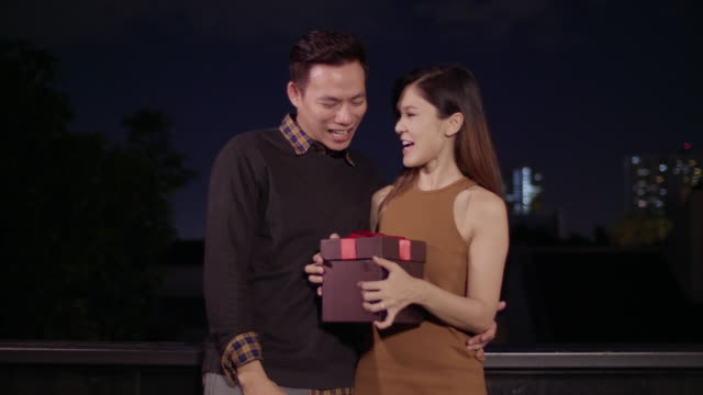 young asian man gives christmas or birthday gift box present to surprise his girlfriend at outdoors on roof terrace with night city in the background, celebration and holiday concept - birthday gift stock videos & royalty-free footage