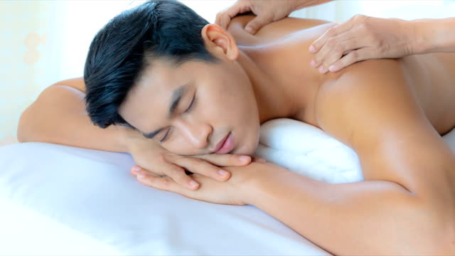 young asian man happiness with receiving a massage theraphy in luxury spa treatment shop, popular relaxation lifestyle in modern city, tourism industry  use, slide shoot, 4k. - massage room stock videos & royalty-free footage