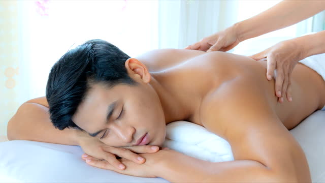 young asian man happiness with receiving a massage theraphy in luxury spa treatment shop, popular relaxation lifestyle in modern city, tourism industry  use, slide shoot, 4k. - massaging stock videos & royalty-free footage