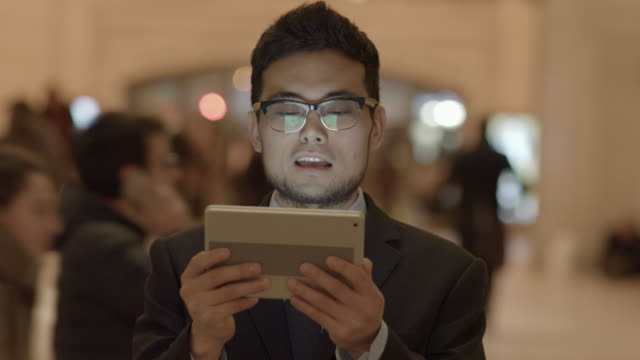 young asian man having a video chat conversation using smart phone tablet pc