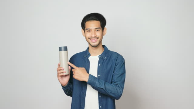 young asian man holding reusable water bottle and looking at camera while standing over grey background, studio shot, zero waste concept - reusable stock videos & royalty-free footage