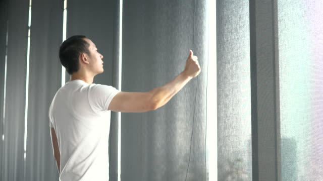 young asian man is trying to open curtain of window at day time - tapparella video stock e b–roll