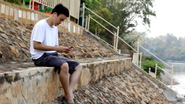 若いアジア人の音楽を聞きながら屋外