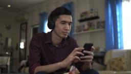Young asian man listening to music at garden at home