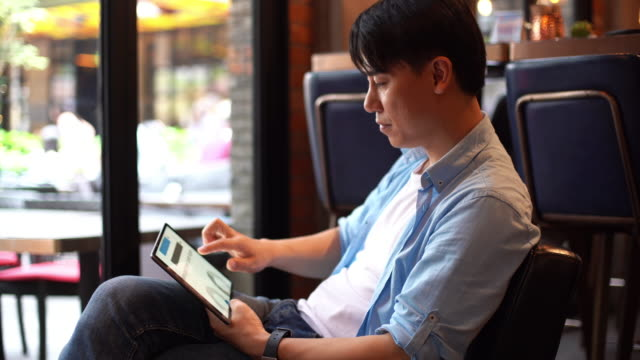 young asian man looking business report on  digital tablet - report document stock videos & royalty-free footage