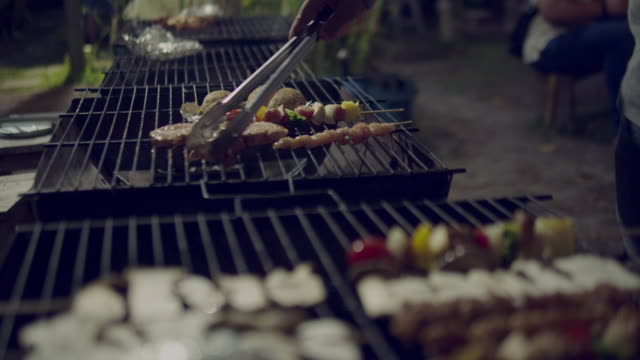 young asian man making barbecue roasted on charcoal grill - pollo ai ferri video stock e b–roll