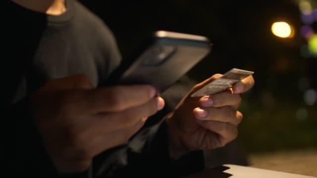 junge asiatische mann bestellen online von ihrem handy mit einer kreditkarte - smooth stock-videos und b-roll-filmmaterial