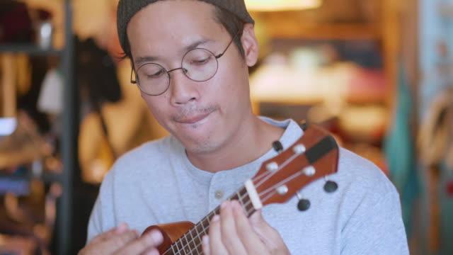 vídeos de stock, filmes e b-roll de homem asiático novo que joga um ukulele no quarto. - ukulele
