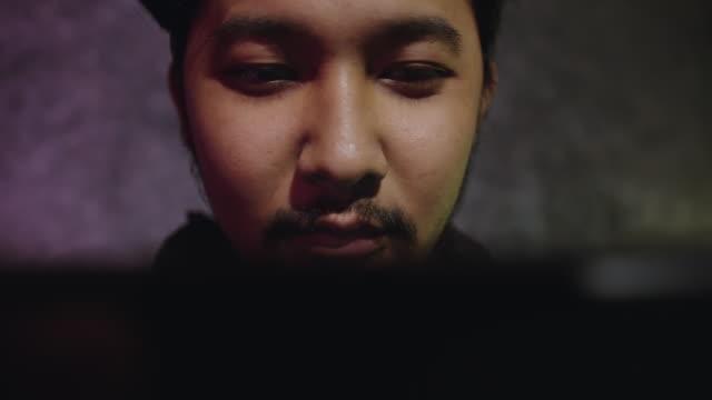 junge asiatische mann spielt ein videospiel mit controllern auf einem schlafzimmer - interaktivität stock-videos und b-roll-filmmaterial