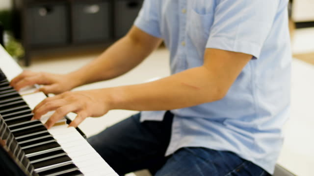 young asian man playing piano at home - adult stock videos & royalty-free footage