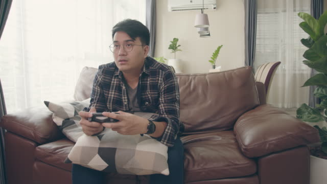 young asian man playing video game in living room at home. concentrated asian guy playing with joystick at modern living room. - computer game control stock videos & royalty-free footage