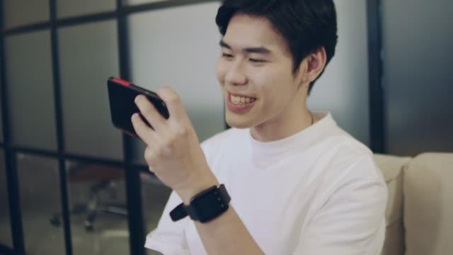 若いアジア人は、スマートフォンでビデオゲームをプレイし、自宅でソファの上に座っています。 - 勝つ点の映像素材/bロール