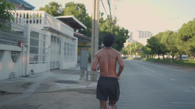 vídeos de stock e filmes b-roll de young asian man running training in a beautiful sunny day in morning. - andar depressa
