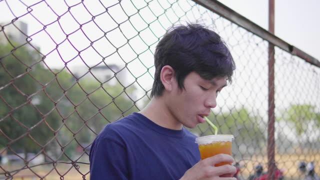 vídeos de stock, filmes e b-roll de jovem asiático sentado e usando telefone inteligente - smart