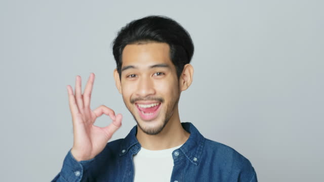young asian man smiling and showing his okay sign, happy asia male looking at camera while showing ok gesture standing over grey background in studio, head shot, 4k resolution - gesturing stock videos & royalty-free footage