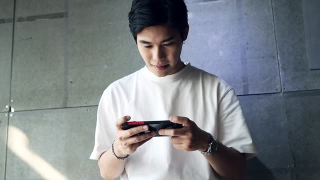 young asian man standing playing a game on the phone with happiness - east asian ethnicity stock videos & royalty-free footage