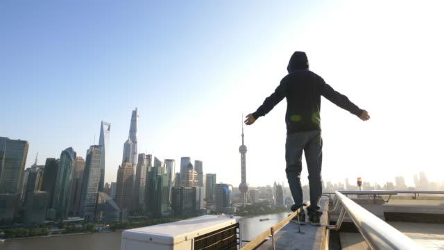 vidéos et rushes de jeune homme asiatique se trouve dans la ville moderne - risque