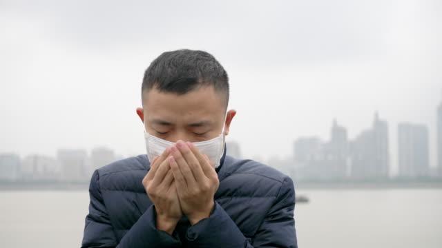 vídeos de stock, filmes e b-roll de jovem asiática fica com máscara branca - tossindo