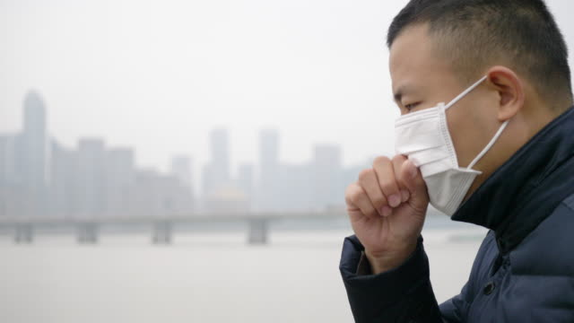 young asian man stands with white mask - smog stock videos and b-roll footage