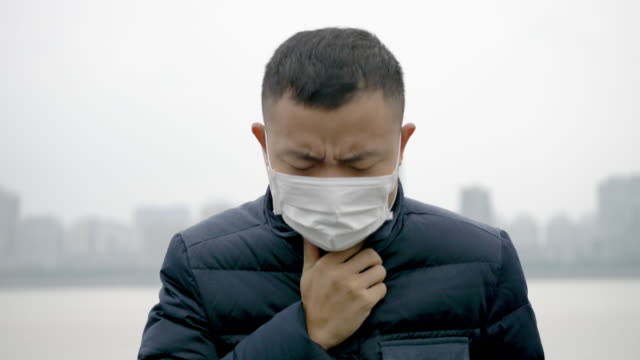 young asian man stands with white mask - air pollution stock videos & royalty-free footage